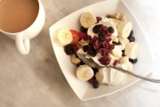Healthy breakfast serving of assorted fruit with blueberries, strawberries , sliced fresh banana and raisins on fresh creamy yoghurt with tea