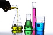 Laboratory Glassware containing different colored liquids agains
